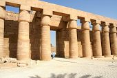 Imposing columns and small Egyptian in the Temple of Amon-Re, Karnak, Luxor, Egypt