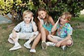 Group of children sitting in park with mobile phones