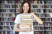Woman Model College Student With Book At Library Holds Bunch Of Book, Look Smart, Smiling To Camera. poster
