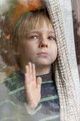 The little boy behind a wet window