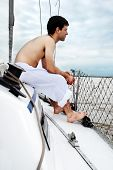 The young man sitting onboard yacht