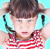 Upset little green eyed girl with pigtails over green background