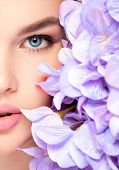 Beautiful young blonde woman with flowers near face -isolated on white. Pretty model  cares of a fac poster