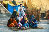 ALLAHABAD, INDIA - FEBRUARY 11: Typical indian family sitting in front of his hut on Kumbh Mela the