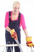Happy Woman Cutting Timber With A Handsaw