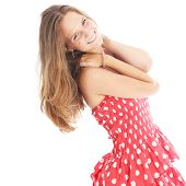 image of vivacious  - Happy carefree teenage girl in a trendy red and white polka dot dress smiling vivaciously as she flicks her long blonde hair - JPG