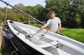stock photo of dingy  - Middle aged man cleaning his dingy boat in his back yard after a day - JPG