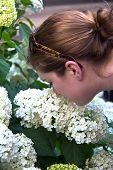 Closeup Of Head Of Young Woman Bending Over And Smelling White Flowers