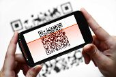 stock photo of qr-code  - Two hands holding a mobile phone scanning a QR code - JPG