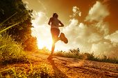 stock photo of horizon  - Young lady running on a rural road during sunset - JPG