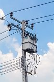 pic of utility pole  - Electric pole against blue sky with white clouds - JPG