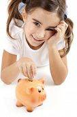 stock photo of insert  - Little girl lying on floor and inserting a one euro coin on the piggy - JPG