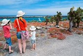 Mother and two kids hiking at scenic terrain on Galapagos South Plaza island