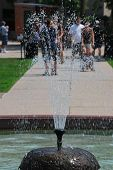 People Walking Behind A Fountain