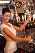 stock photo of bartender  - Portrait of attractive female bartender tapping mug of beer in pub - JPG