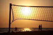 Sunset Beach com silhueta de pessoas e beachball líquido em primeiro plano.