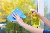 pic of trigger sprayer bottle  - Hands with  napkin cleaning  window - JPG