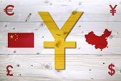 pic of yuan  - Chinese Yuan and the other currency units on white wooden world map - JPG