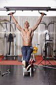 Athletic man doing hanging legs raise