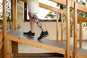 stock photo of prosthesis  - Male prosthesis wearer training to climb a unaided in a speical parcour or interior area where surfaces have been laid out to simulate realistic environmental situations - JPG