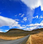 Improbable form the clouds created by glaciers, shine under the sun. Gray dirt road in the Chilean national park to