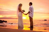 Just married couple on tropical beach at sunset, Intimate loving moment at wedding