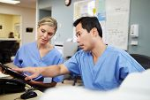 foto of nursing  - Male And Female Nurse Working At Nurses Station - JPG
