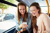 picture of commutator  - Two Young Women Reading Text Message On Bus - JPG