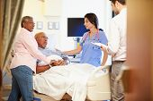 stock photo of geriatric  - Medical Team Meeting With Senior Couple In Hospital Room - JPG