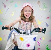 Happy Little Girl On A Bicycle. Painted Wall Background.