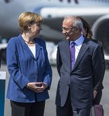 BERLIN, GERMANY - MAY 20, 2014: German Chancellor Angela Merkel (L), Turkish Minister of transport Lutfi Elvan (R) open up the International aviation and space exhibition ILA.