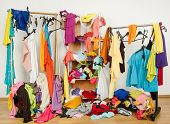 Untidy cluttered woman wardrobe with colorful clothes and accessories.