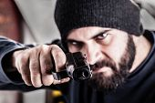 stock photo of pistols  - a bearded criminal pointing a pistol and wearing a beanie hat isolated over white - JPG