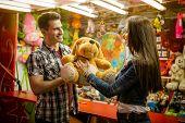 Smiling boyfriend giving gift his girlfriend on amusement park