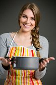Portrait of cheerful housewife in apron holding saucepan