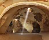 Clay huge caves are picturesquely shined with the sun from an opening above and lateral entrances. The ray of sunlight at an angle gets into space of  cave and forms dazzling circle on a rough floor