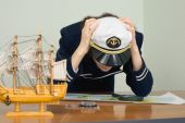 Woman In Uniform Of Sea Captain Concentrated Thinks Over A Map