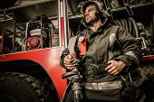 stock photo of fireman  - Firefighter near truck with equipment with water water hose over shoulder - JPG
