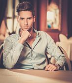 Handsome young man alone in a restaurant
