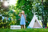 picture of teepee  - Adorable little girl having fun playing outdoors on summer day - JPG