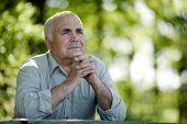 Elderly Man Sitting In The Garden Thinking