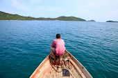 A fisherman seat in front of his boat