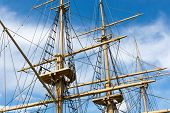 pic of big-rig  - Masts and rigging of a big old sailing ship in front of a blue sky - JPG