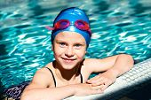 stock photo of bathing  - beautiful girl in a bathing suit swim cap goggles holding on overboard in a swimming pool - JPG