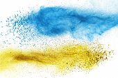Blue and yellow powder explosion isolated on white