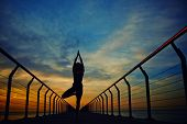 Perfect silhouette of a slender woman engage yoga on the sea with sunrise