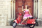 Young and sexy woman with her motor scooter and a vintage photo camera - retro style image.