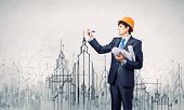 stock photo of engineering construction  - Young man engineer drawing sketches of construction project - JPG