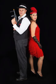 picture of tommy-gun  - Dangerous bonny and clyde gangster with 1920 style clothes standing with a gun - JPG