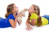 picture of twin baby girls  - happy twin sister kid girls kissing puppy dog lying playing on white background - JPG